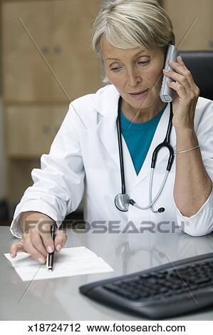 banque de photo personne agee docteur f minin utilisation t l phone bureau bureau. Black Bedroom Furniture Sets. Home Design Ideas