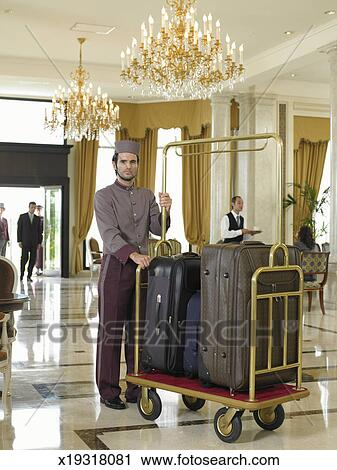 Stock Photography Of Bellboy Holding Luggage Trolley In