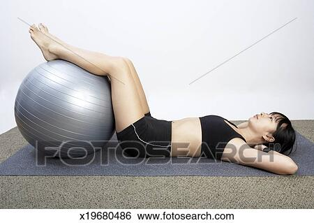 Stock Images of Young woman lying on back with legs on ...