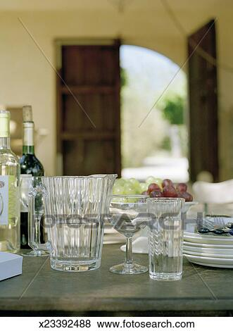 Pictures of Glass water jug and bottles of wine on dining ...