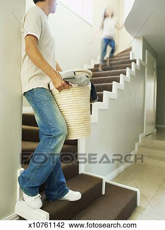 Side Profile Of A Father Carrying Clothes In A Laundry Basket Down The  Stairs