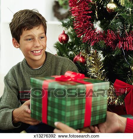 Colecci n de foto chico joven 10 11 aceptando un regalos delante de un rbol de - Regalos chico joven ...