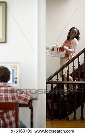 Stock Image   Woman Walking Down Stairs Carrying Laundry Basket. Fotosearch    Search Stock Photos