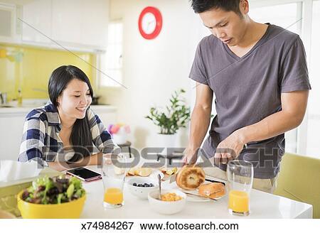 Beeld jong paar vervaardiging bagel voor breakfast x74984267 zoek stock fotografie - Muurschildering volwassen kamer ...