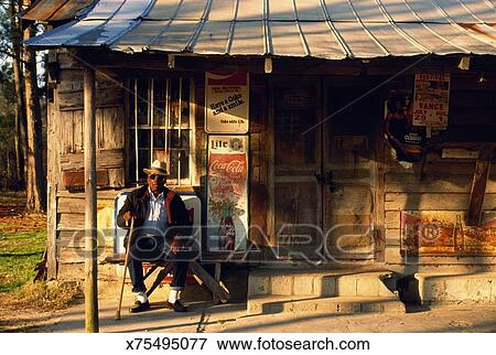 Picture of Mature man sitting outside old general store, South ...
