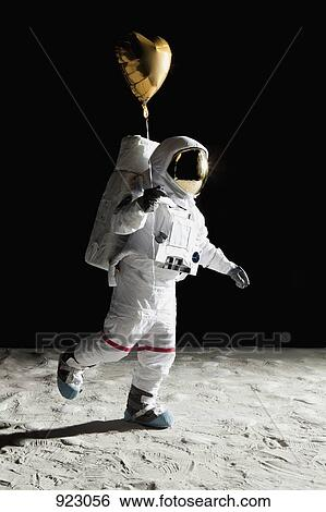 stock images of an astronaut on the moon holding a heart