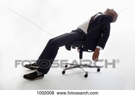 An Exhausted Businessman Sleeping In An Office Chair