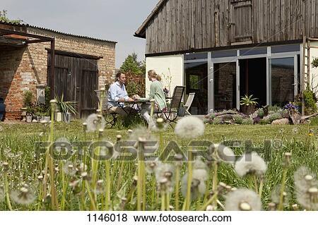 Immagini uno coppia sedendo ad tavola in loro for Disegni cortile anteriore per semplice casa ranch