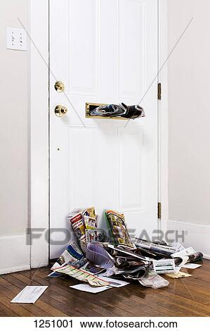 Inside Front Door Clipart stock photography of newspapers stuck in a mail slot above a heap