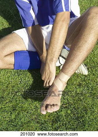 Stock Photography of A soccer player taping up his ankle ...