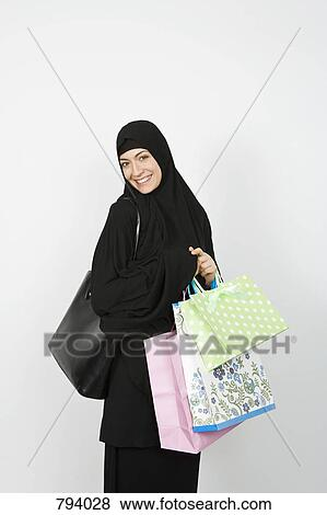 Fantastic Mixed Race Woman Wearing Winter Clothing Holding Shopping Bags Texting
