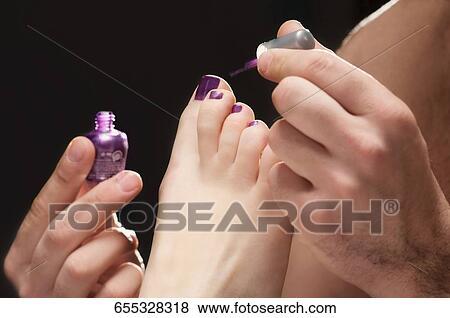 Image , gros plan, de, a, main homme, demande, vernis à ongles, sur, les, femme, ongles orteil