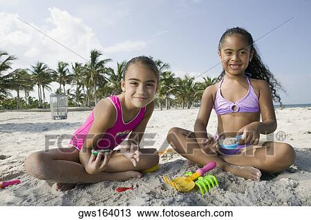 Portrait of two girls sitting on the beach and playing with sand - Stock Photo.