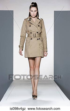 Model Wearing Beige Raincoat On Catwalk At Fashion Show