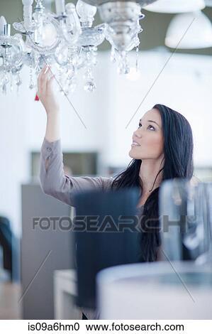banques de photographies achats femme pour lustre dans magasin is09a6hm0 recherchez des. Black Bedroom Furniture Sets. Home Design Ideas