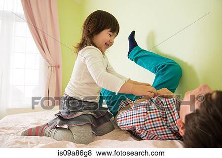 bilder m dchen kitzeln bruder bett is09a86g8 suche stockfotos bilder print fotos und. Black Bedroom Furniture Sets. Home Design Ideas