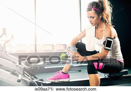 Stock Photo of Young woman holding water bottle in gym ...