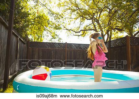 Stock photo of girl in swimming goggles in garden paddling for Garden paddling pools