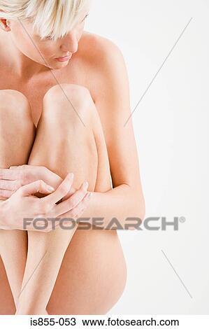 Nude woman hugging legs