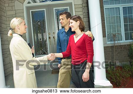Stock Photo of Real estate owner selling home to young couple 2 ...