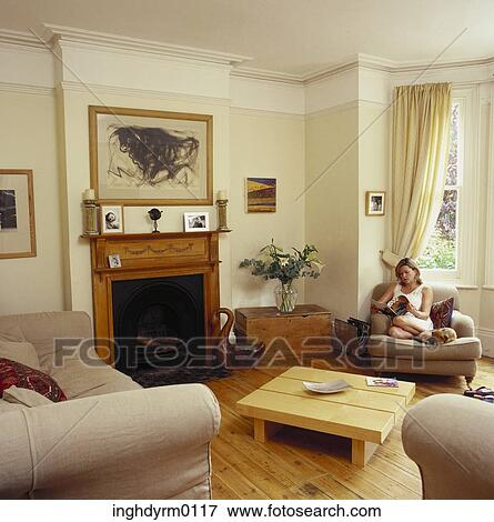 bild frau sitzen auf a couch in a wohnzimmer lesen zeitschrift inghdyrm0117 suche. Black Bedroom Furniture Sets. Home Design Ideas