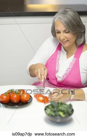 Stock Image of Mature woman slicing tomatoes at table is09ap7dp ...