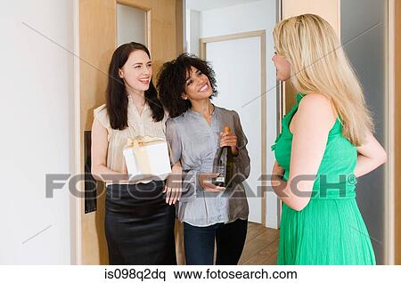 Stock Image - A woman greeting friends at the door. Fotosearch - Search Stock Photos