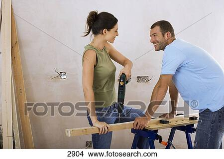 banque de photo couple faire bricolage chez soi femme forage trou perceuse. Black Bedroom Furniture Sets. Home Design Ideas