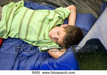 Boy (8-10) lying on sleeping bag in tent entrance eyes closed sleeping with hands behind head side view & Stock Image of Boy (8-10) lying on sleeping bag in tent entrance ...
