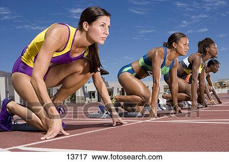 Picture of Female runners at starting block kneeling on race track ...