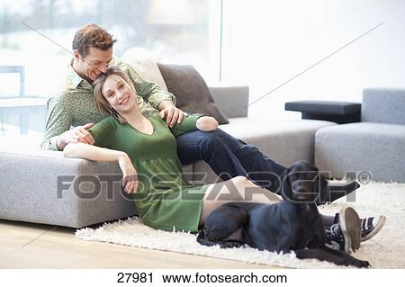stock fotografie junges sitzen in wohnzimmer mit hund frau mit amputierte arm 27981. Black Bedroom Furniture Sets. Home Design Ideas