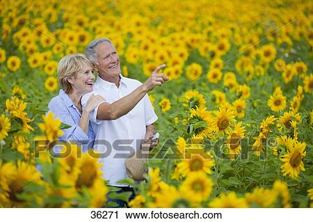 Archivio fotografico sorridente coppia indicare tra - Soleggiato in inglese ...