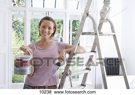 picture 20s woman home decorating indoors with paint brush and ladder fotosearch