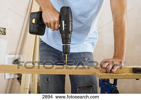 banque de photo homme faire bricolage chez soi forage trou dans morceau de bois. Black Bedroom Furniture Sets. Home Design Ideas