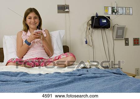 Stock Photography of Girl (9-11) sitting in hospital bed ...