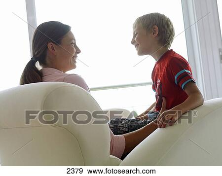 Mother and son (5-7) sitting in chair at home, smiling, face to face ...