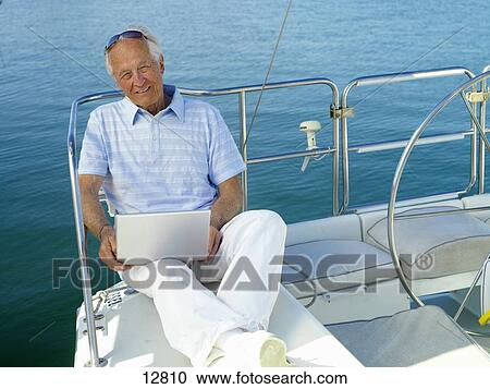 Stock Photography of Senior man on boat with laptop ...