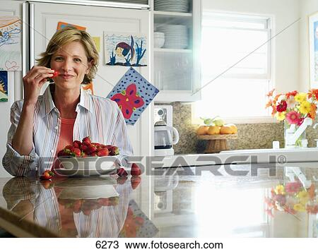 Stock Photo of Woman sitting at breakfast table in kitchen, eating ...