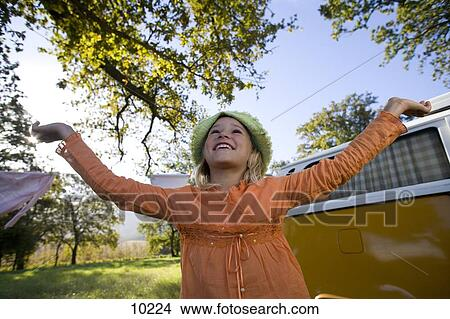 Stock photo of girl 9 11 with arms raised by camper van for 9 11 mural van