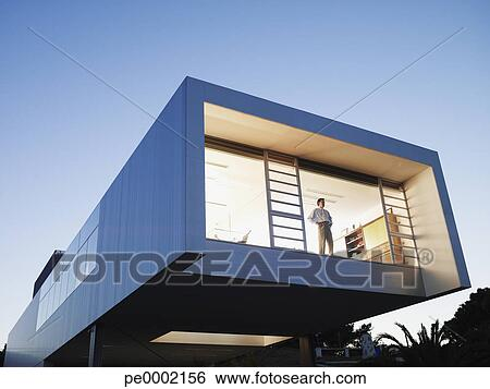 modern office exterior. exterior of a modern office building with man looking out window