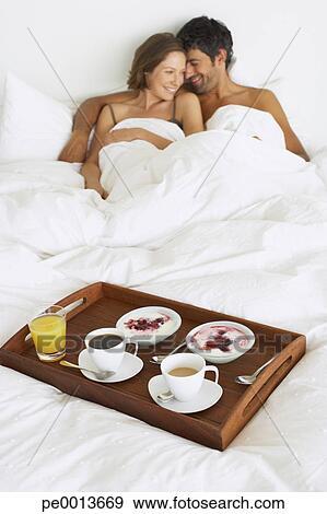 Archivio fotografico donna in uomo letto con vassoio - Vassoio colazione letto ...
