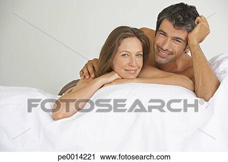 banques de photographies femme homme coucher dans lit pe0014221 recherchez des images des. Black Bedroom Furniture Sets. Home Design Ideas