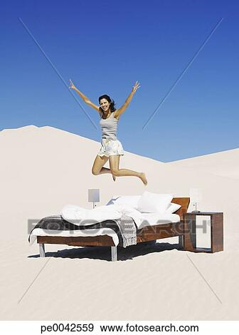 stock fotograf a frau springende auf a bett drau en pe0042559 suche stock fotografie. Black Bedroom Furniture Sets. Home Design Ideas