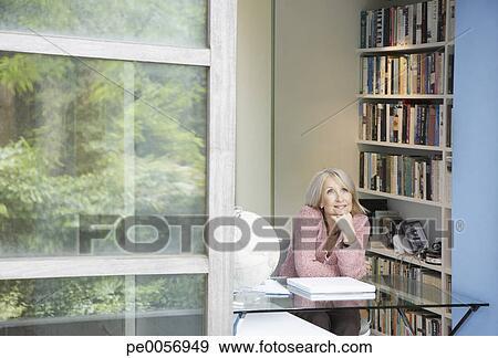 banque de photographies femme regarde dehors fen tre dans bureau maison pe0056949. Black Bedroom Furniture Sets. Home Design Ideas
