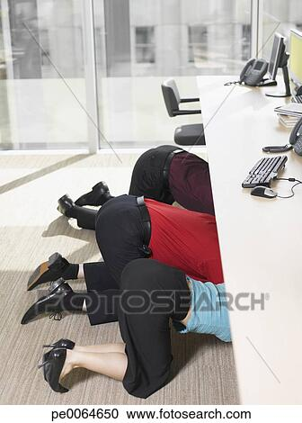 Stock Photography Of Businesspeople Hiding Under Desk In