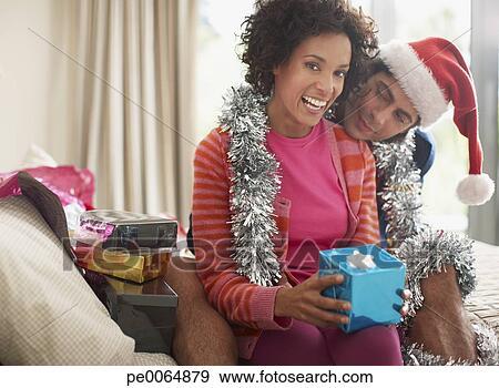 stock fotograf mann aufpassen ehefrau offenes weihnachtsgeschenk pe0064879 suche stock. Black Bedroom Furniture Sets. Home Design Ideas