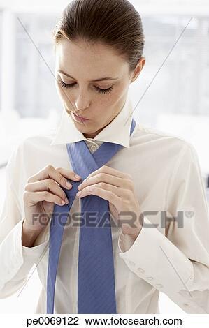 banque de photo femme affaires mettre cravate pe0069122 recherchez des images des. Black Bedroom Furniture Sets. Home Design Ideas