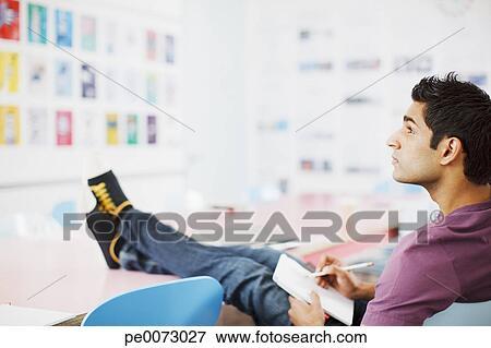 image homme criture sur bloc notes pieds haut dans bureau pe0073027 recherchez des. Black Bedroom Furniture Sets. Home Design Ideas