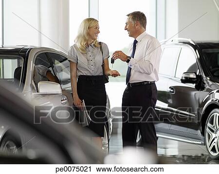 banques de photographies vendeur remettre femme clef voiture dans automobile salle. Black Bedroom Furniture Sets. Home Design Ideas