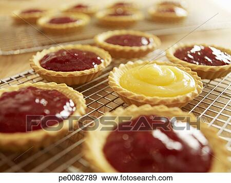 Stock photograph of close up of jam tarts cooling on wire for Easy jam tarts ready made pastry